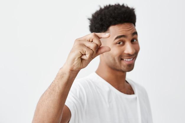 Só um pouco. foco suave. retrato isolado de jovem macho de pele escura bonito com cabelos cacheados em t-shirt branca casual gesticulando com a mão, olhando na câmera com o rosto feliz e relaxado