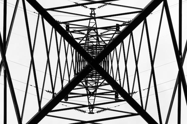 Sob a torre da linha eléctrica de alta tensão aérea. vista da parte inferior da construção
