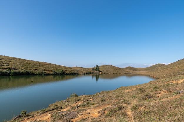Sob o céu azul, o lago natural no prado tem grama amarela e água azul