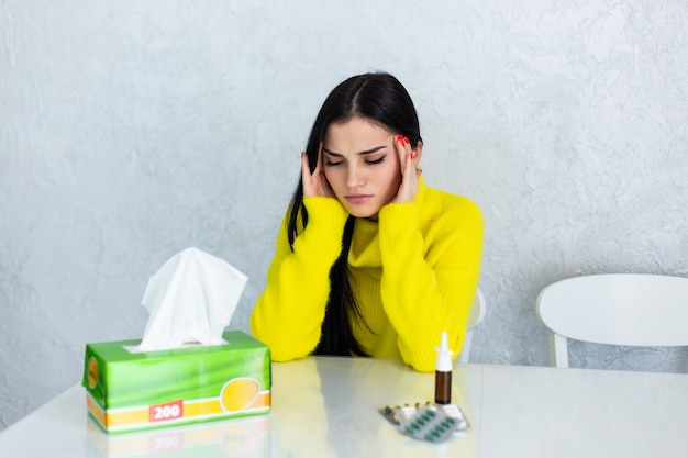 Sob o tempo. mulher jovem e doente, sentindo-se mal e assoando o nariz enquanto tem um cobertor sobre os ombros e sentada no sofá com os olhos fechados e mesa com comprimidos à sua frente