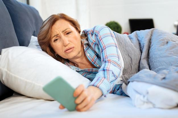 Sob um cobertor grosso. mulher madura chateada pegando o smartphone da mesa de cabeceira e verificando o tempo na tela enquanto está deitada na cama