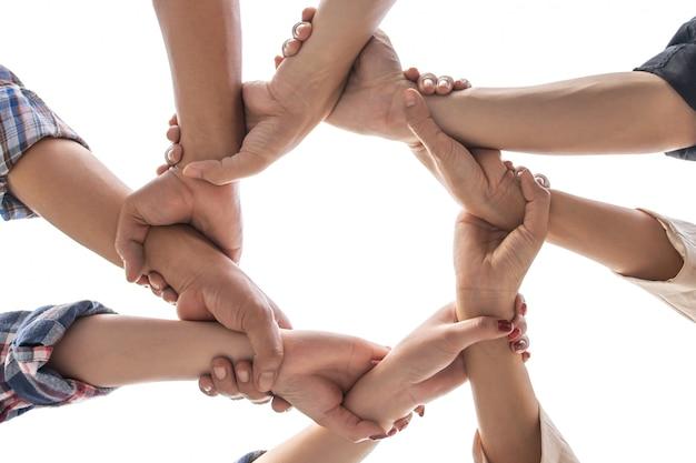 Sob vista amizade pessoas parceria trabalho em equipe cruzou as mãos no fundo branco