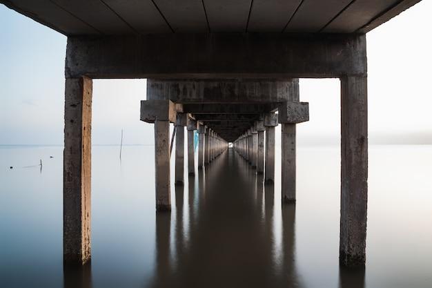 Sob vista da ponte estendida para o mar com reflexo de água