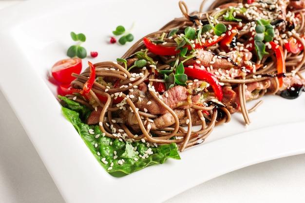 Soba macarrão de trigo sarraceno com fatias de carne, legumes frescos e molho de soja, cozinha asiática