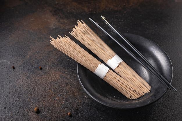 Soba, trigo sarraceno, macarrão cru, pronto para cozinhar refeição lanche na mesa cópia espaço comida fundo
