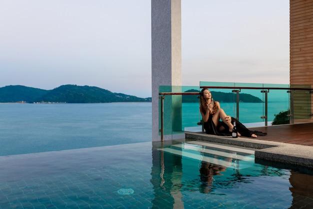Soberba jovem garota em um vestido preto longo senta-se com uma taça de champanhe perto da piscina de beiral infinito, excelente vista para o mar