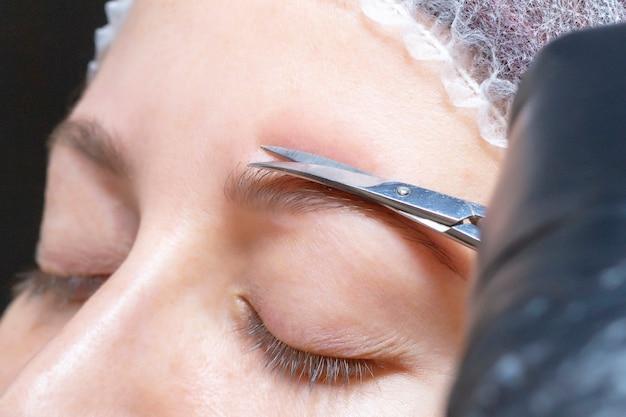 Sobrancelha que dá forma em um salão de beleza. a menina é cortada com uma tesoura para obter um cabelo extra nas sobrancelhas