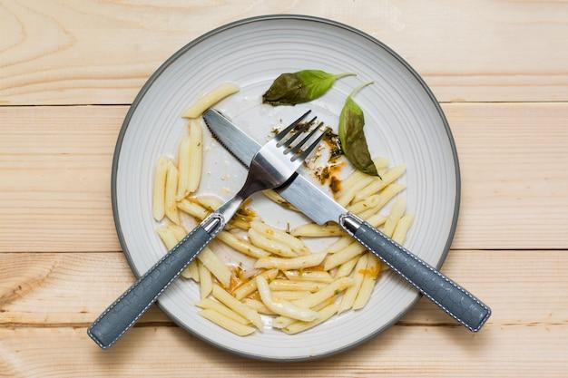 Sobras de almoço e talheres em um prato