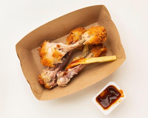 Sobras de coxinhas de frango com caixa de ketchup intocada