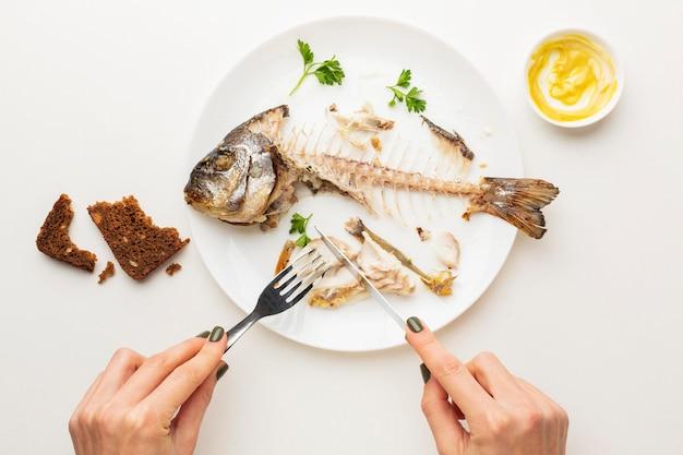 Sobras de peixe cozido e mãos