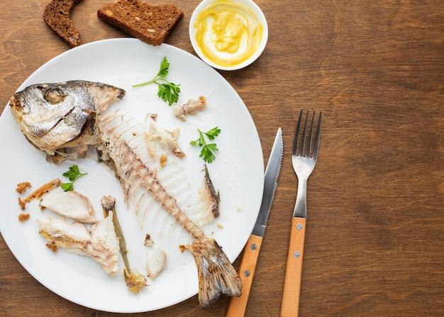Sobras de peixe cozido e talheres