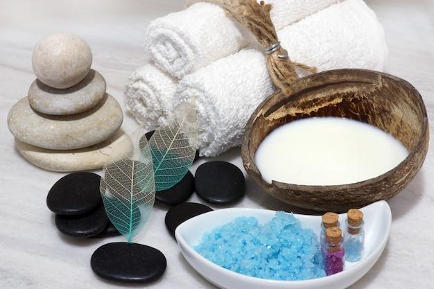 Sobre a bancada de mármore branco encontra-se um conjunto para procedimentos de spa com leite de coco, leite rejuvenescedor, pedras e sal de banho azul.