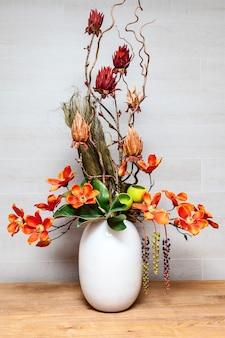 Sobre a mesa da sala há um vaso branco com composição floral, arranjo floral