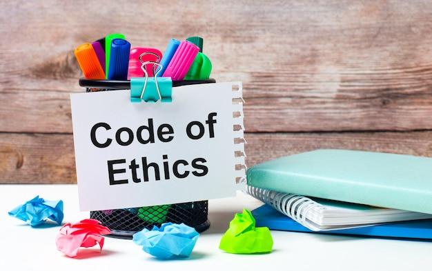 Sobre a mesa e contra o fundo de uma parede de madeira, há um estande com canetas hidrocor multicoloridas, papéis brilhantes e uma folha de papel com o texto código de ética
