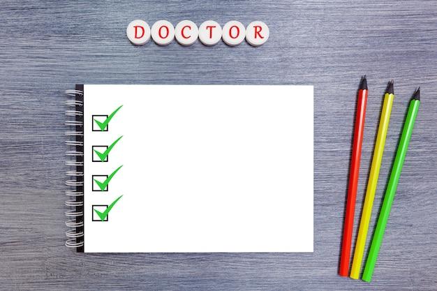 Sobre a mesa está um caderno branco com três lápis bloco de notas com lápis e comprimidos