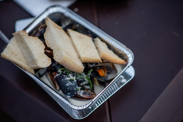 Sobre a mesa está um prato de alumínio descartável contendo mexilhões assados no forno em molho de alho, polvilhados com queijo parmesão e uma baguete fresca crocante. comida rápida para viagem na rua no festival. copie o espaço