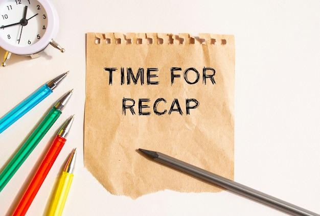 Sobre a mesa está uma folha amarrotada de papel kraft, rasgada de um caderno. texto na folha time for recap. canetas coloridas, relógio e lápis. conceito para o seu projeto.