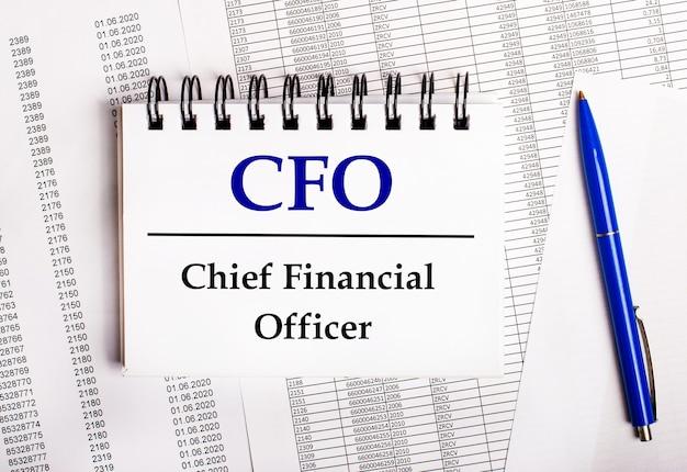 Sobre a mesa estão gráficos e relatórios, nos quais estão uma caneta azul e um bloco de notas com a palavra cfo chief financial officer
