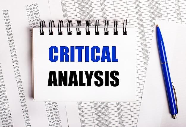 Sobre a mesa estão gráficos e relatórios, nos quais estão uma caneta azul e um caderno com a palavra análise crítica