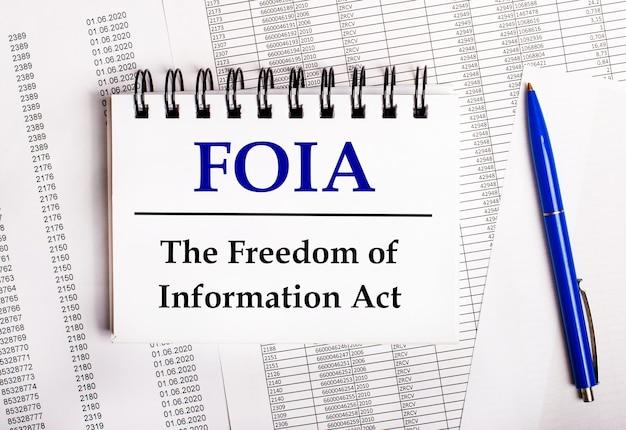 Sobre a mesa estão gráficos e relatórios, nos quais estão uma caneta azul e um caderno com a palavra foia. a lei de liberdade de informação