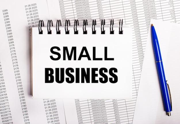 Sobre a mesa estão gráficos e relatórios, nos quais estão uma caneta azul e um caderno com as palavras pequenas empresas