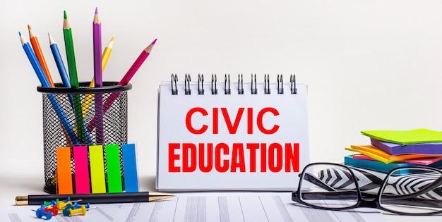 Sobre a mesa estão lápis de cor em um suporte, adesivos de cores vivas, óculos e um caderno com a inscrição educação cívica