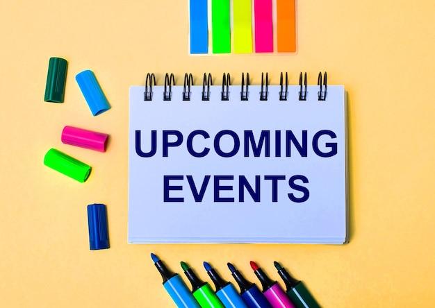 Sobre a mesa estão lápis de cor em um suporte, adesivos de cores vivas, óculos e um caderno com a inscrição próximos eventos