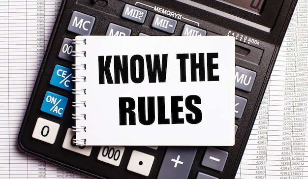 Sobre a mesa estão os relatórios, uma calculadora e um cartão com as palavras conheça as regras. conceito de negócios