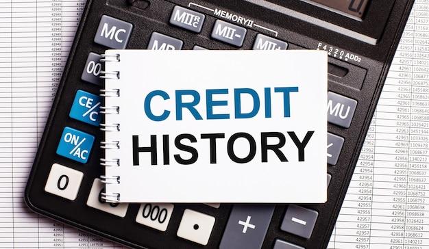 Sobre a mesa estão os relatórios, uma calculadora e um cartão com as palavras histórico de crédito. conceito de negócios