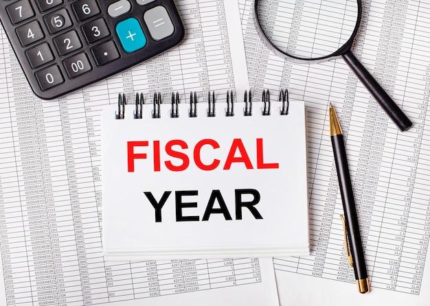 Sobre a mesa estão os relatórios, uma lupa, uma calculadora, uma caneta e um caderno branco com a inscrição ano fiscal. conceito de negócios