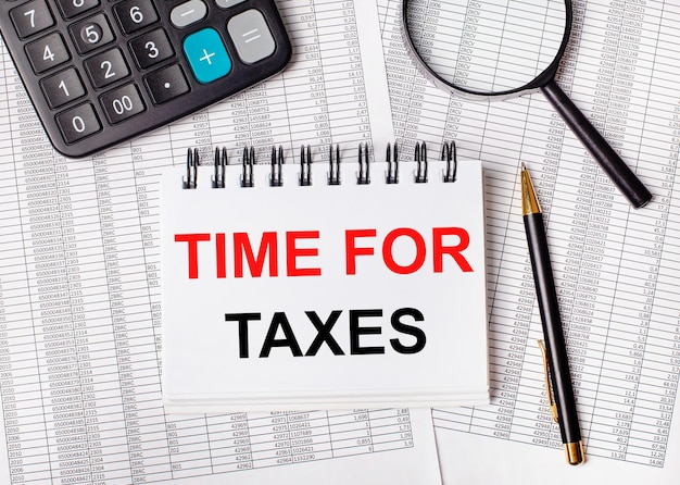 Sobre a mesa estão os relatórios, uma lupa, uma calculadora, uma caneta e um caderno branco com a inscrição tempo dos impostos. conceito de negócios