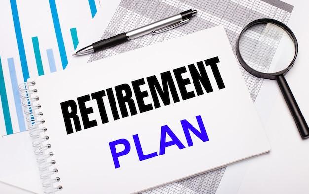 Sobre a mesa estão relatórios, diagramas, uma caneta, uma lupa e um bloco de notas branco com o texto do plano de aposentadoria. conceito de negócios