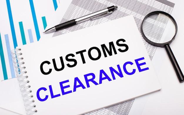Sobre a mesa estão relatórios, diagramas, uma caneta, uma lupa e um bloco de notas branco com texto customs clearance. conceito de negócios