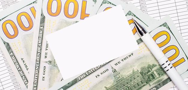 Sobre a mesa estão relatórios, dinheiro, uma caneta e um cartão branco em branco