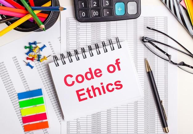 Sobre a mesa estão relatórios, uma calculadora, lápis de cor e adesivos, uma caneta e um caderno com o texto código de ética