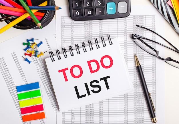 Sobre a mesa estão relatórios, uma calculadora, lápis de cor e adesivos, uma caneta e um caderno com o texto para fazer lista