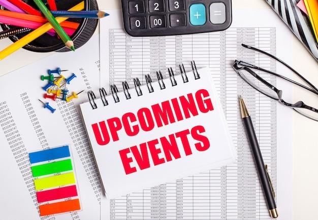 Sobre a mesa estão relatórios, uma calculadora, lápis de cor e adesivos, uma caneta e um caderno com o texto próximos eventos