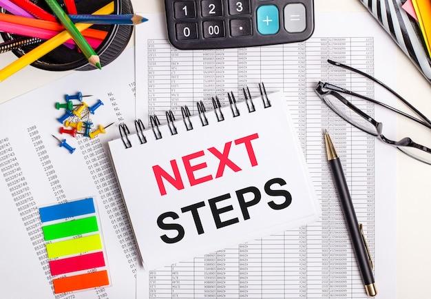 Sobre a mesa estão relatórios, uma calculadora, lápis de cor e adesivos, uma caneta e um caderno com o texto próximos passos