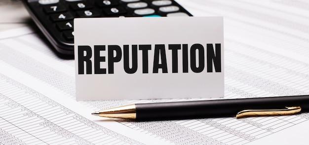 Sobre a mesa estão relatórios, uma caneta, uma calculadora e um cartão branco com o texto reputação