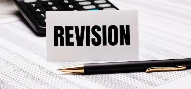 Sobre a mesa estão relatórios, uma caneta, uma calculadora e um cartão branco com o texto revisão