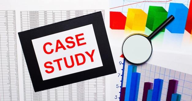 Sobre a mesa há relatos de gráficos multicoloridos, uma lupa e uma folha de papel em moldura preta com o texto estudo de caso. conceito de negócios