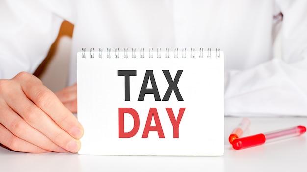 Sobre a mesa há um marcador vermelho e um bloco de papel branco no qual está escrito o texto - dia do imposto, letras vermelhas e pretas