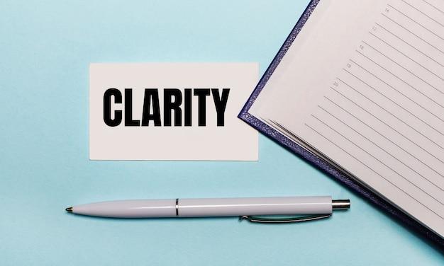 Sobre fundo azul claro, caderno aberto, caneta branca e cartão com o texto clareza