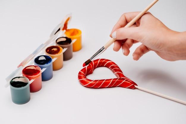 Sobre fundo branco, tintas multicoloridas para desenho. pincel de madeira nas mãos com tinta vermelha, garota desenha um coração de caramelo. dia dos namorados.