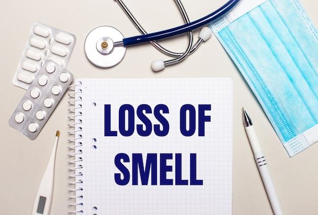 Sobre fundo cinza claro, máscara facial descartável azul claro, estetoscópio, termômetro eletrônico, comprimidos, caneta e caderno com a inscrição perda de cheiro. conceito médico
