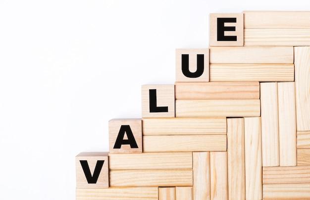 Sobre fundo claro, blocos de madeira e cubos com o texto valor