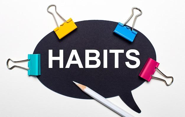 Sobre fundo claro, clipes multicoloridos, lápis branco e papel preto com as palavras hábitos. vista de cima