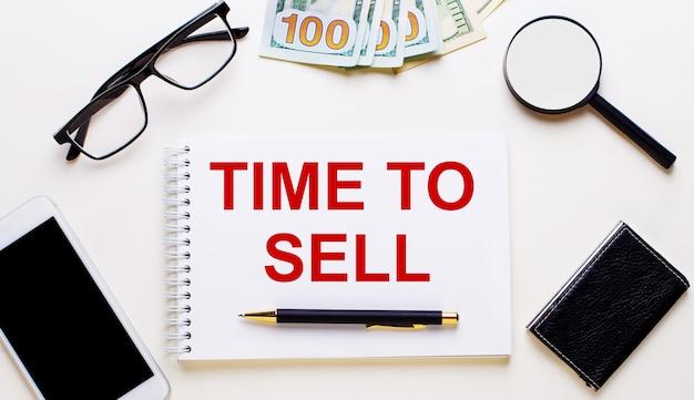 Sobre fundo claro, dólares, óculos, lupa, telefone, caneta e caderno com a inscrição hora de vender. conceito de negócios