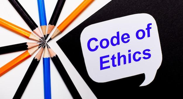 Sobre fundo claro, lápis multicolorido e sobre fundo preto cartão branco com a inscrição código de ética.