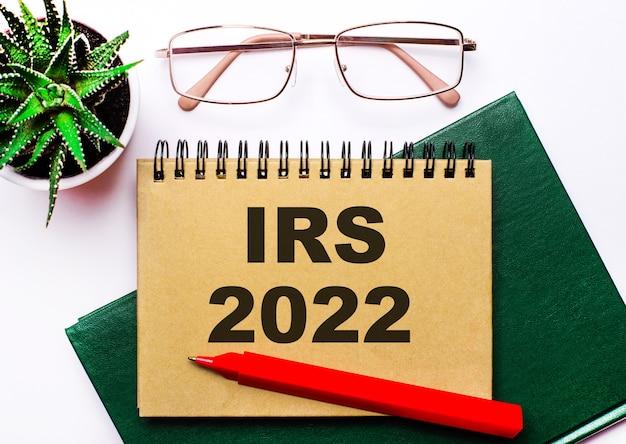 Sobre fundo claro, óculos de armação dourada, flor em vaso, caderno verde, caneta vermelha e caderno marrom com o texto irs 2022. conceito de negócio